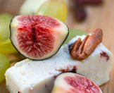 Figs and cheese presnsted as snacks.