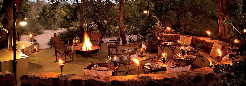 The boma area of an exclusive African safari lodge lit by lanterns and firelight.