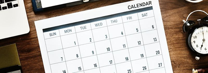 A calendar on a desk with other office items.