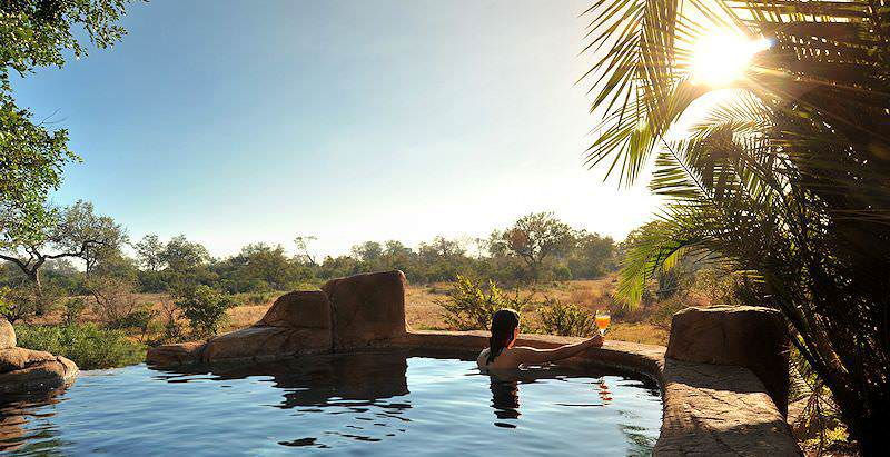A guest lounges pool side at Lukimbi Safari Lodge in the Kruger National Park.