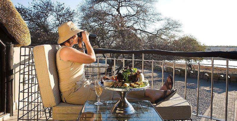 A guest at Namutoni Camp looks out over Etosha National Park with her binoculars.