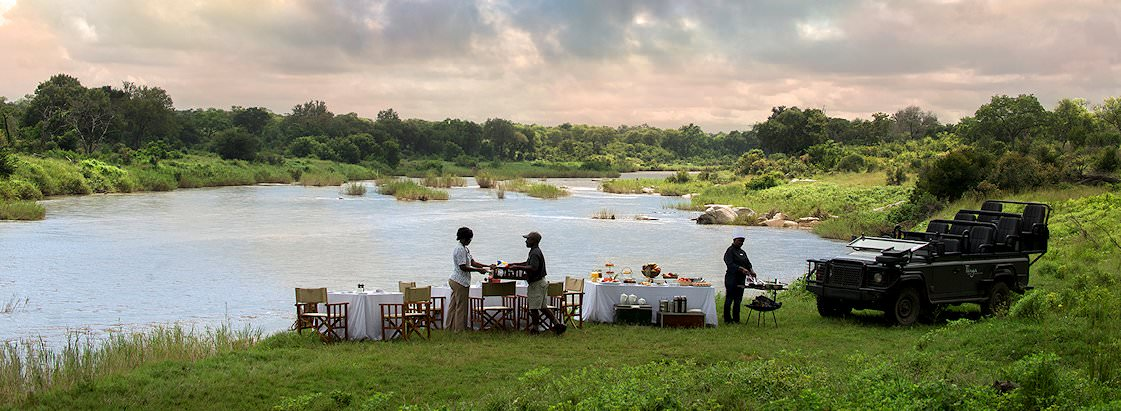 A bush picnic is set up for guests on the bank of the Sabie River.