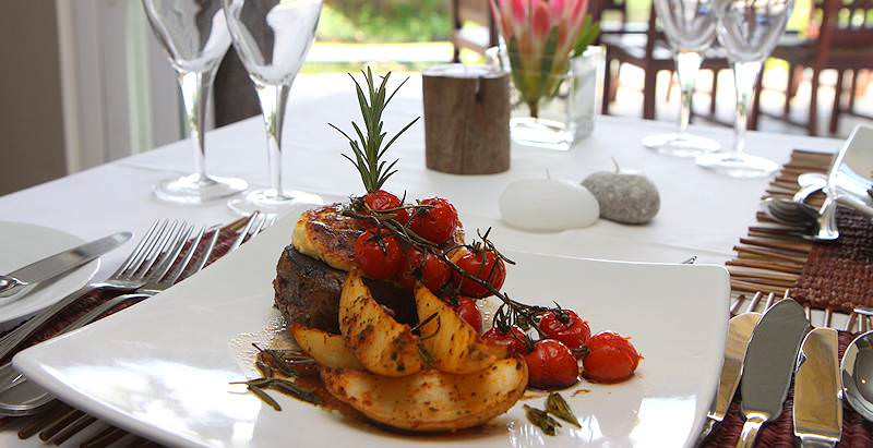 Fillet mignon served with roast potatoes and vine tomatoes.