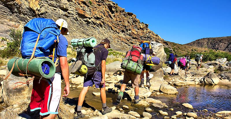 Travelers taking on the Fish River Canyon trail in Namibia.