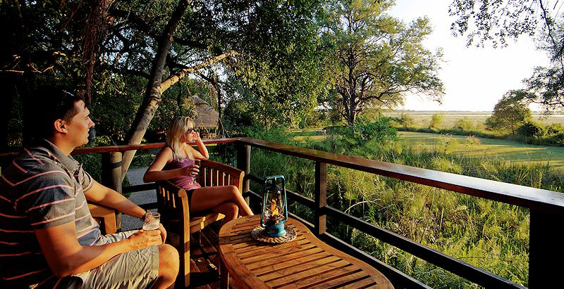 Guests unwind on the deck of their safari lodge in the Okavango Delta.