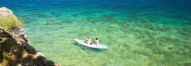Travelers kayak across the crystal-clear waters of the Quirimbas Archipelago.