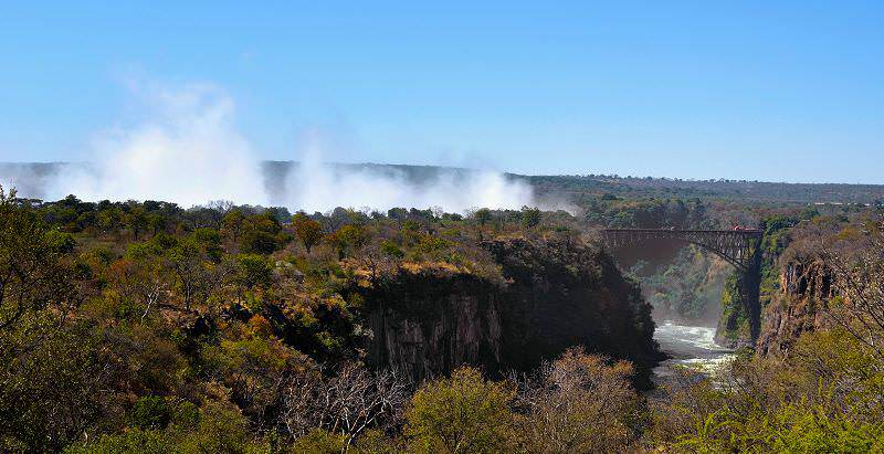 The mists of the Victoria Falls rise up above the Mosi-oa-Tunya National Park.