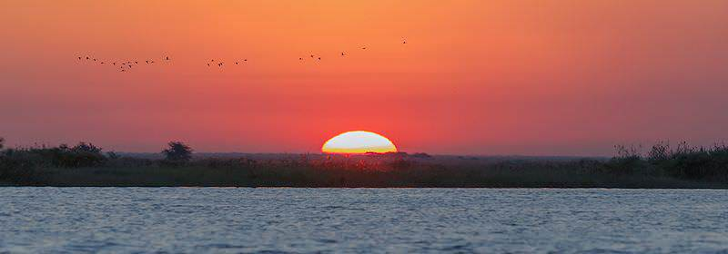 The sun sets over the Chobe River in Botswana.