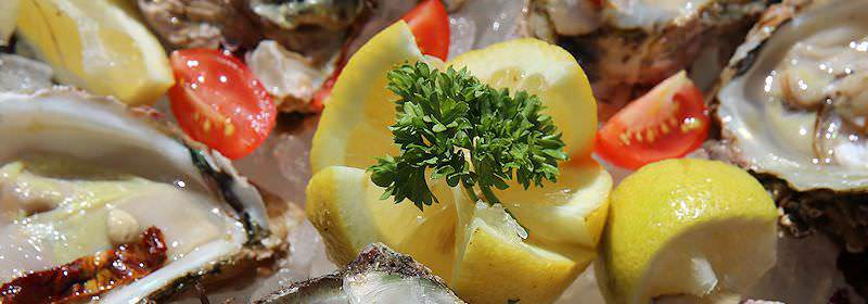 Oysters garnished with lemon, cherry tomatoes and parsley.