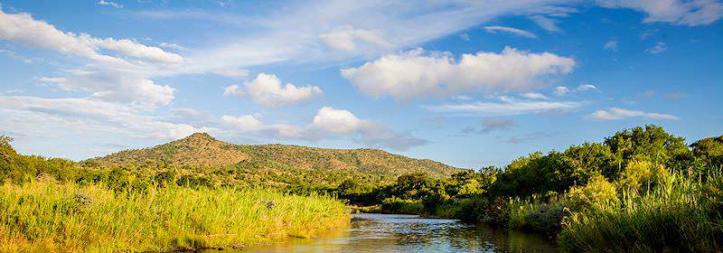 A river trundles through the Hluhluwe-iMfolozi Game Reserve.