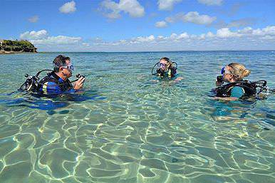 Beginner scuba divers test their equipment in the shallows.