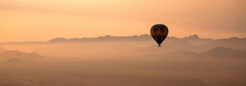 A hot air balloon floats above Sossusvlei.