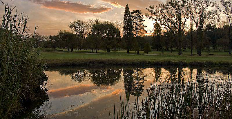 A dreamy sunset is reflected in the placid waters of a water hazard along the Royal Johannesburg Golf Course.