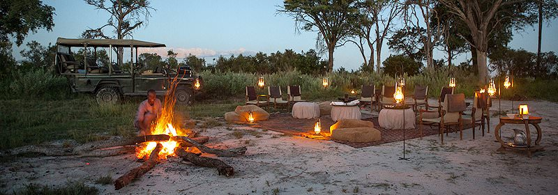 A private outdoor dining experience set up in the wilderness.