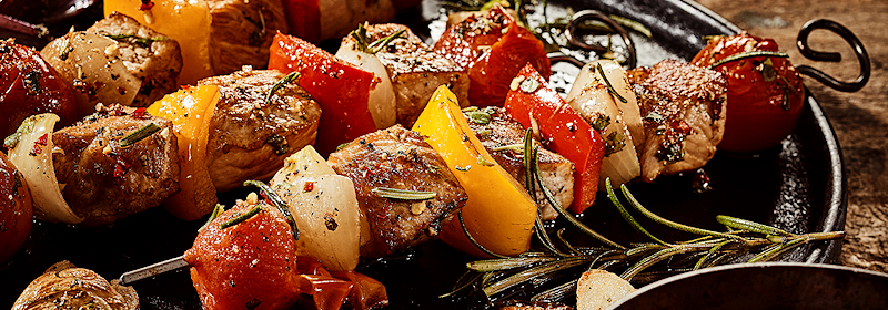 Delicious kebabs laid out on a platter with rosemary.
