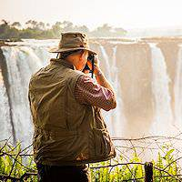 A traveler takes a snapshot of the Victoria Falls.