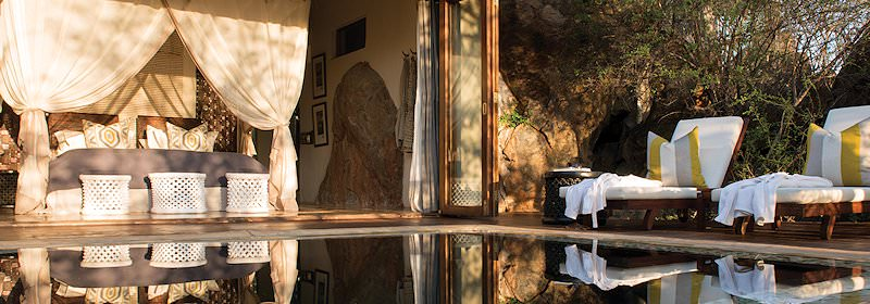 An expansive private plunge pool in front of a luxurious suite at a safari lodge.