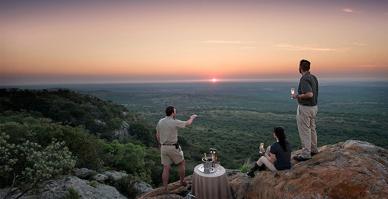A honeymoon couple enjoys champagne in the bush with their guide during the 7 Day East Coast Safari and Beach Honeymoon.