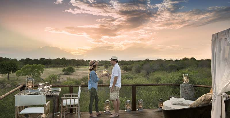 A couple enjoys a sunset drink during the 4 Day Private Lodge Safari.