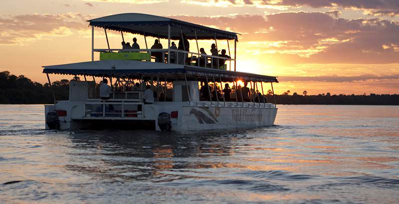 A sunset cruise on the Zambezi River during the 14 Day Cape Town, Wine, Kruger and Vic Falls Tour.
