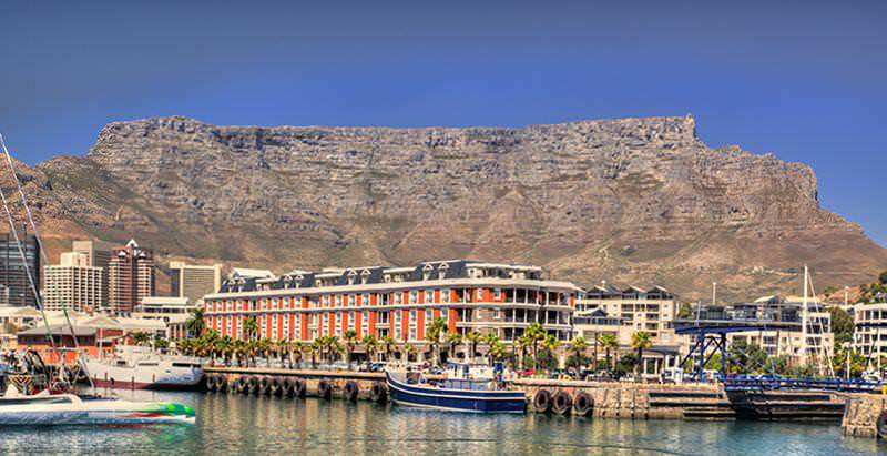 Table Mountain looms above the Victoria & Alfred Waterfront, which features on the 10 Day Cape Town to Vic Falls Tour.