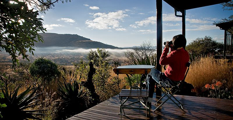 A guest at Three Tree Hill Lodge looks out over the Drakensberg during the 10 Day Tiny Kingdoms Tour.