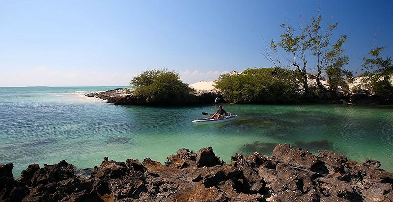A guest canoes near Coral Lodge during the 5 Day Tropical Mozambique Package.