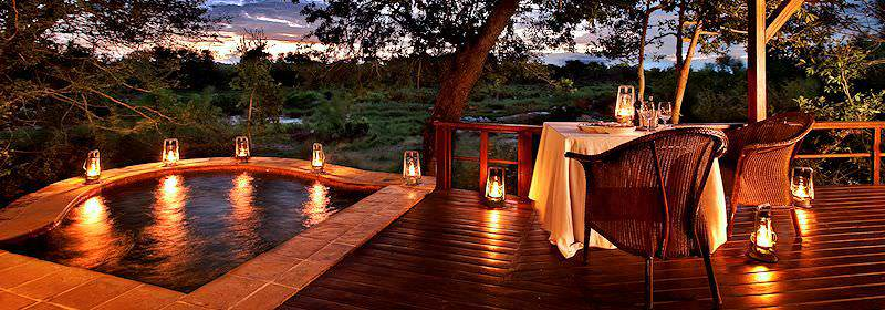 The lantern-lit private deck and plunge pool of a luxury suite at Lion Sands Tinga Lodge.