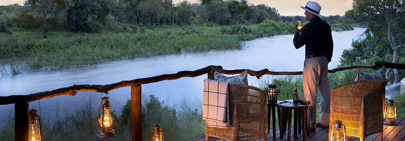 A guest enjoys an early evening sundowner on the lanter-lit deck of a safari lodge.