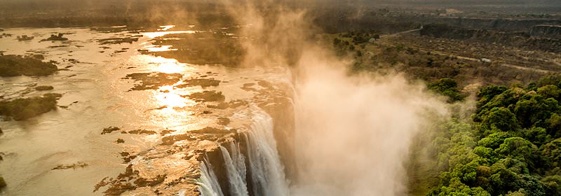 The setting sun glances off the water at the edge of the Victoria Falls.