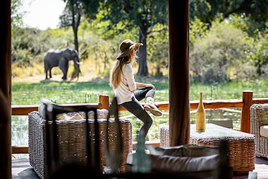 A guest observes an elephant from the deck at Chief's Camp.