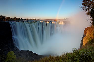 A rainbow at sunset over the Victoria Falls.