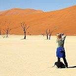 A traveler taking a photo of a dune in Sossusvlei.