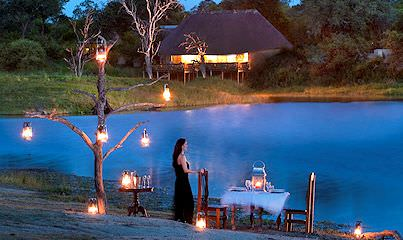 A guest at Arathusa Safari Lodge gets ready to sit down for a private bush dinner.