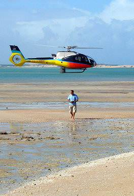 A guest is dropped off on a Mozambican island by helicopter transfer.